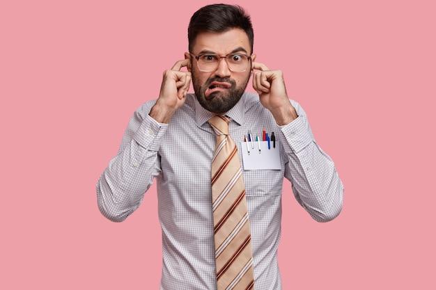 Le patron masculin mécontent et ennuyé est habillé formellement, se bouche les oreilles, ne veut pas entendre les plaintes de ses collègues, fronce les sourcils avec mécontentement