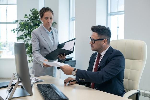 Patron passant un document signé à sa secrétaire
