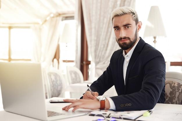Un patron sérieux regarde droit, se prépare pour une réunion d'affaires avec un ordinateur portable au restaurant