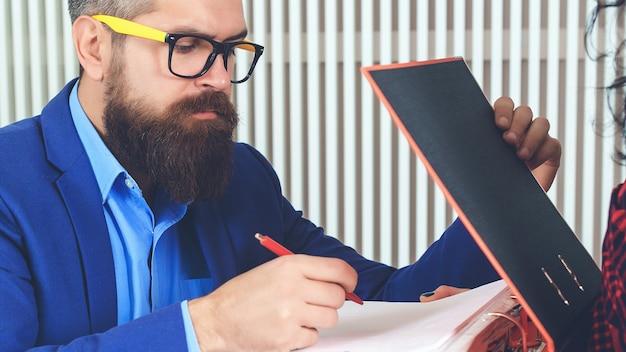 Le patron signe les papiers. une femme secrétaire donne à son patron des documents papier ou un contrat à signer. notion de coopération.