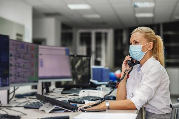 Patronne blonde dévouée et travailleuse en costume avec masque facial assis dans la salle de contrôle d'une installation de chauffage et ayant une conversation téléphonique importante pendant l'épidémie de virus corona.