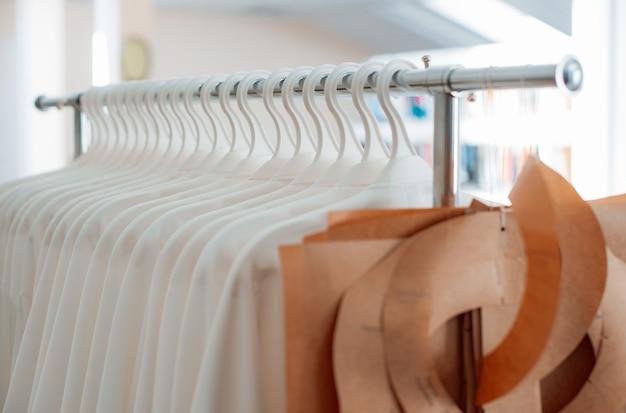 Patrons de couture et vêtements sur cintres sur l'atelier de confection