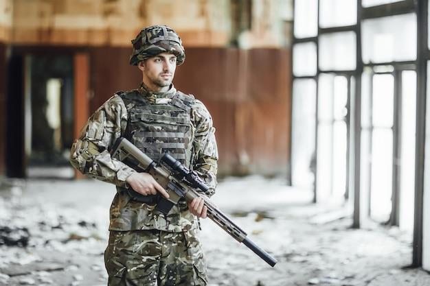 Patrouille le territoire. jeune soldat dans l'armée se tient à la fenêtre du bâtiment effondré
