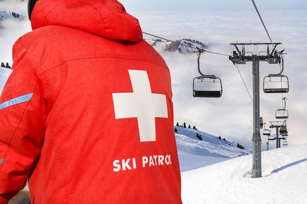 Un patrouilleur de ski vêtu d'une veste rouge avec une croix blanche dans le dos. téléski au sommet de la montagne