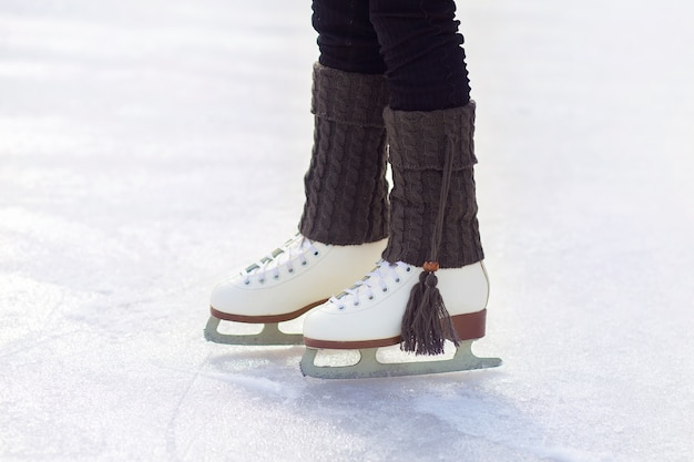Les pattes des patins artistiques sont sur la glace sur la patinoire. gros plan de patins blancs classiques. jambières chaudes tricotées à pompons