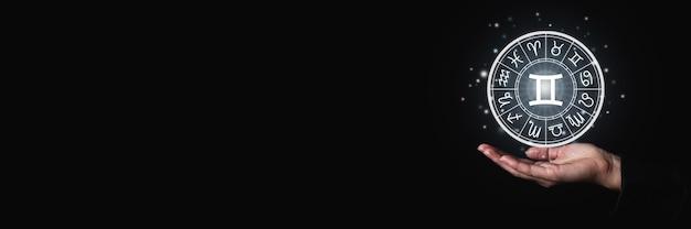 La paume femelle tient un signe lumineux avec des symboles de signes du zodiaque dans l'obscurité. bannière.