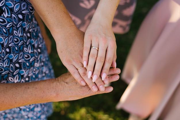 La paume d'une grand-mère, mère et fille avec des anneaux de mariage. la relation entre les trois générations