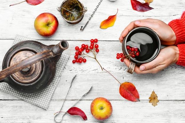 Paume de votre main avec une tasse de thé d'automne