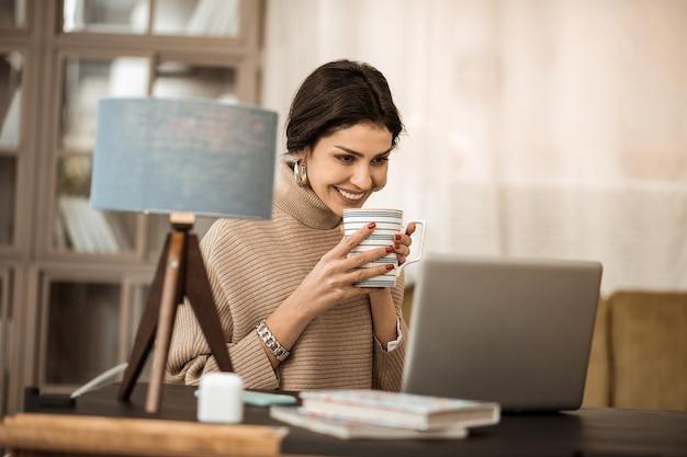 Pause au travail. rire belle dame avec des boucles d'oreilles dorées regardant sur l'écran tout en étant de bonne humeur