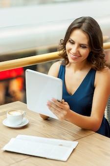 Pause café. une belle jeune femme prenant une pause tout en travaillant avec une tablette numérique au restaurant