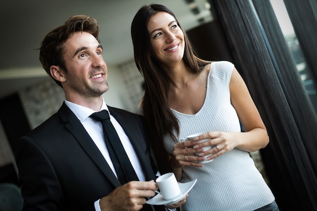 Pause café. couple de jeunes collègues en tenue de soirée debout sur le lieu de travail, buvant du café près de la fenêtre