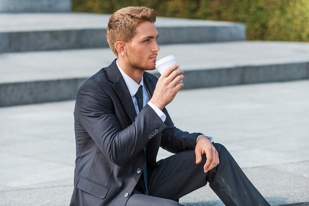 Pause café. gentil jeune homme en tenue de soirée buvant du café assis à l'extérieur