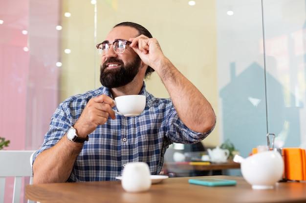 Pause café. homme d'affaires agréable barbu réussi portant des lunettes ayant une pause-café à la cafétéria