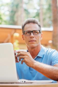 Pause café. homme mûr réfléchi buvant du café et regardant loin alors qu'il était assis dans un café-terrasse