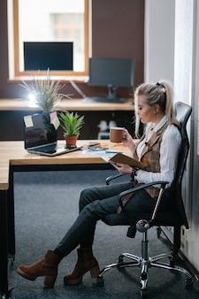 Pause café. il est temps de redémarrer et de se détendre. femme assise dans un bureau moderne et confortable avec une tasse de boisson revigorante en examinant ses notes