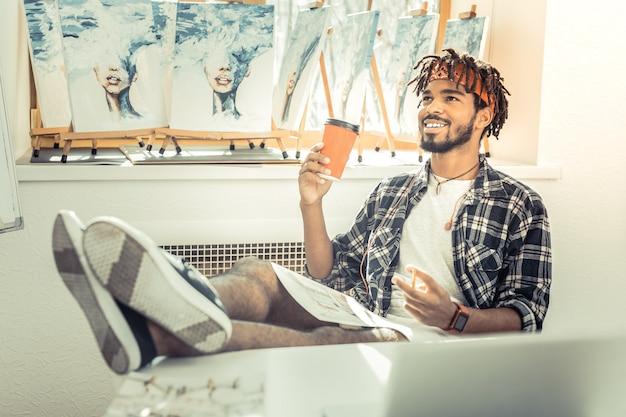 Pause café. jeune artiste talentueux prometteur se sentant soulagé pendant une pause-café