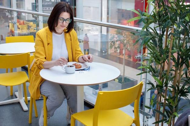 Pause café. jeune fille brune dans une veste jaune avec des lunettes