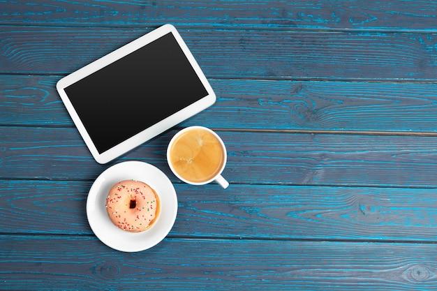 Pause café, une tasse de café, beignet et tablette sur la vue de dessus de table