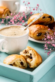Pause de vacances avec tasse de café, mini pain au chocolat croissants frais et fleurs d'oeillet sur surface turquoise