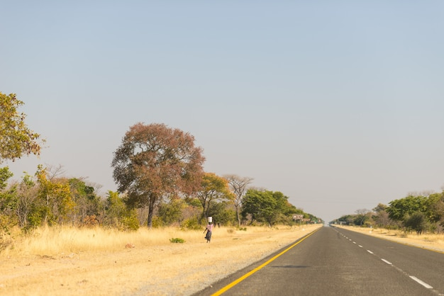 Pauvre femme marchant au bord de la route dans la bande rurale de caprivi, la région la plus peuplée de namibie, en afrique.