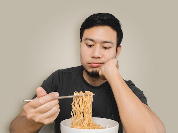 Pauvre homme asiatique se sentir ennuyeux avec la même vieille nouille instantanée.