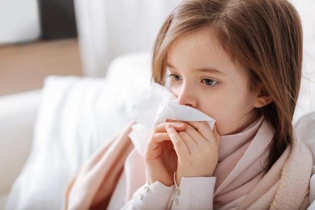 Pauvre petite fille malade à l'aide d'un mouchoir en convalescence à la maison