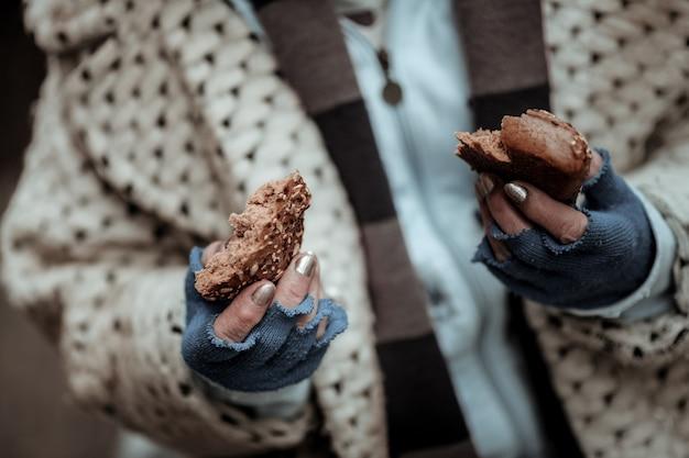Pauvre vie. gros plan de deux morceaux de pain étant entre les mains d'une pauvre femme sans-abri