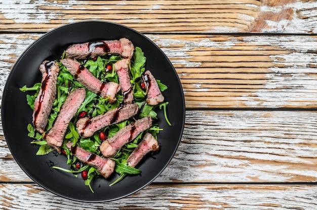 Pavé de boeuf grillé en tranches avec salade de feuilles de roquette. fond en bois blanc. vue de dessus. copiez l'espace.