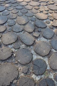 Pavé en bois composé de nombreuses souches de bois sciées rondes creusées dans le sol