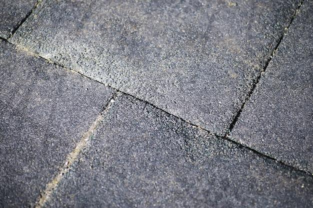 Pavé gris, passerelle piétonne, chaussée en gros plan, la texture, vue de dessus. fond de sol en pierre au carré en brique de ciment. dalles de pavage en béton. dalles de pavage