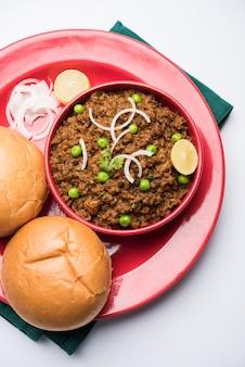 Pavé de mouton kheema ou viande hachée épicée indienne servie avec du pain ou du kulcha, garni de pois verts. fond de mauvaise humeur. mise au point sélective
