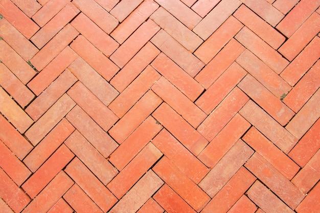 Pavé de pavé rouge à la surface de brique sur un trottoir pour une décoration design intérieure et extérieure.