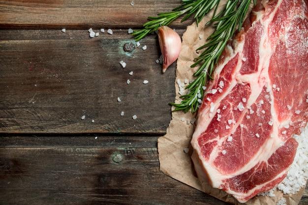 Pavé de porc cru au romarin parfumé. sur un fond en bois.