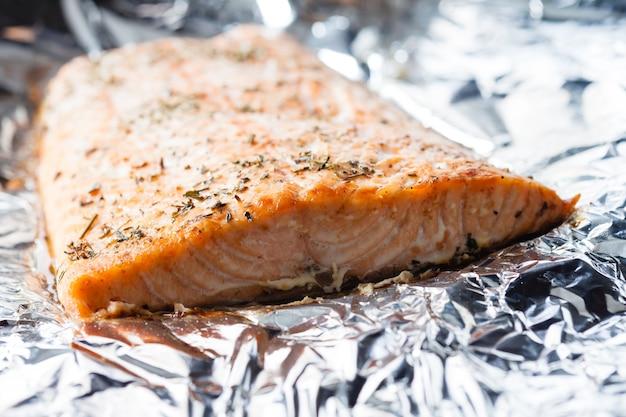 Pavé de saumon appétissant cuit avec des herbes dans du papier d'aluminium