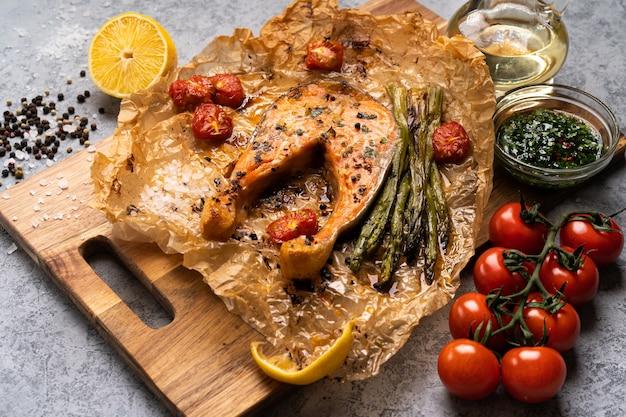 Pavé de saumon au four sur parchemin avec légumes, asperges, tomates sur une table grise.