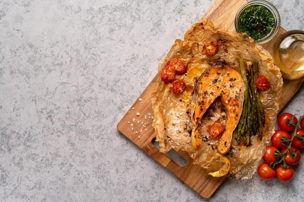 Pavé de saumon au four sur parchemin avec légumes, asperges, tomates