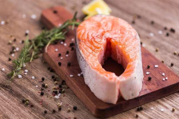 Pavé de saumon cru sur planche de bois