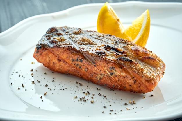 Pavé de saumon grillé appétissant sur charbon de bois avec citron, servi dans une assiette blanche sur une surface en bois sombre. fruits de mer au barbecue