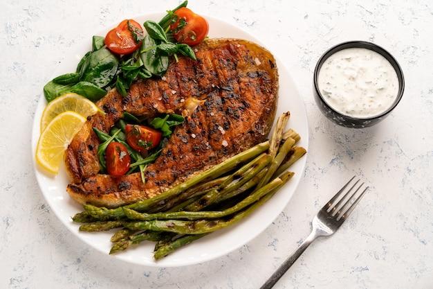 Pavé de saumon grillé, asperges et épinards frais aux tomates sur une plaque blanche sur une table lumineuse.