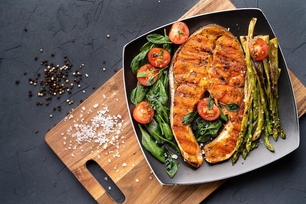 Pavé de saumon grillé, asperges et épinards frais avec des tomates sur une plaque carrée noire sur une table sombre.