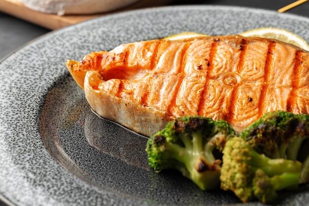 Pavé de saumon grillé au brocoli sur plaque grise close up