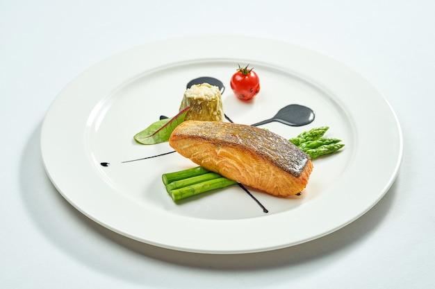 Pavé de saumon grillé aux asperges et sauce balsamique dans une assiette blanche. isolé sur une surface blanche. vue d'en-haut