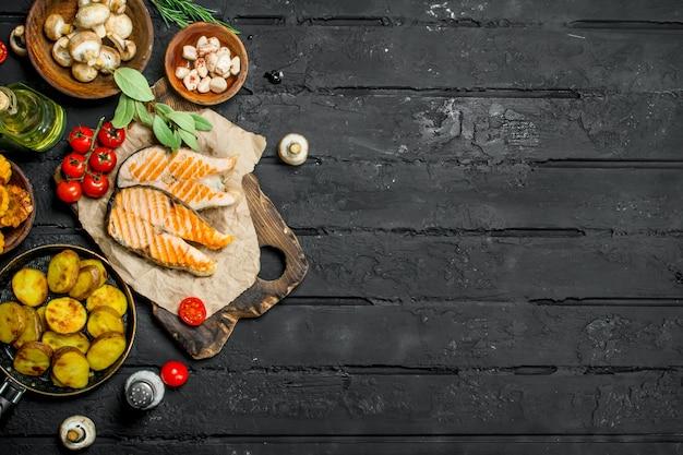 Pavé de saumon grillé aux légumes et épices. sur fond rustique noir.