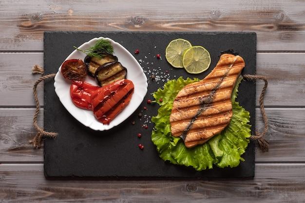 Pavé de saumon grillé fait maison sur des feuilles de laitue sur une planche sombre à côté de légumes rôtis dans le