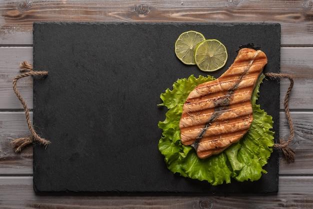 Pavé de saumon grillé fait maison sur des feuilles de laitue sur une planche sombre à côté de quartiers de citron vert