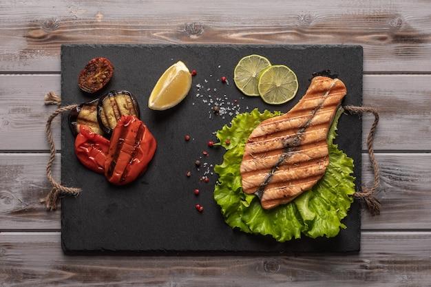 Pavé de saumon grillé fait maison sur des feuilles de laitue servi sur une planche sombre à côté de légumes cuits au four citron vert