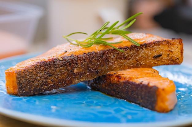 Pavé de saumon grillé un morceau de cuisine maison fraîche avec du poivre noir au romarin et du sel de l'himalaya