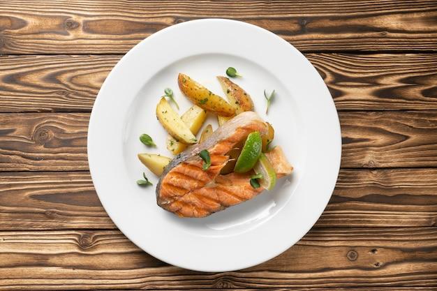Pavé de saumon grillé avec pommes de terre au four et citron vert dans un plateau en céramique blanche