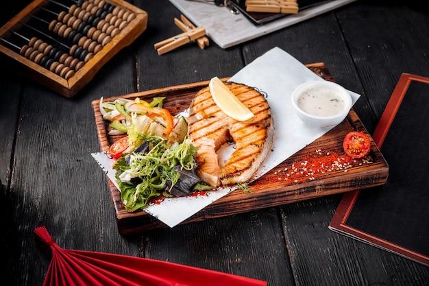 Pavé de saumon grillé avec salade et sauce blanche