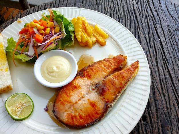 Pavé de saumon grillé avec salade sauce à l'estragon et frites